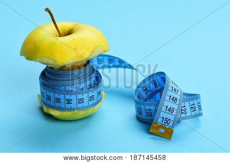 Green Apple Wrapped Tight With Blue Measuring Tape