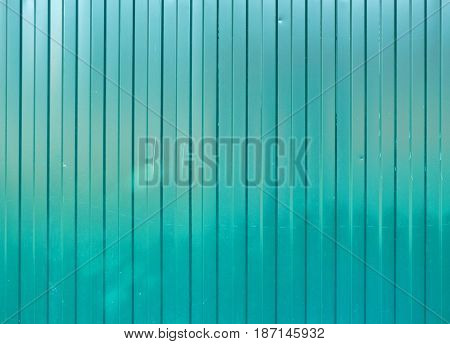 Green goffered metal texture, corrugated steel surface with vertical lines. Striped industrial background with place for text.