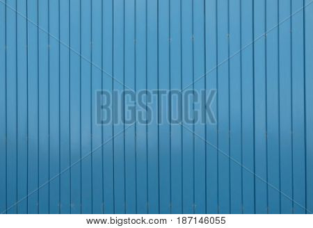 Large blue metal siding wall texture with vertical structure. Some little scratches and screw heads. Industrial background. Goffered steel surface.