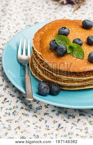 Close up of delicious golden pancakes with fresh blackberries.