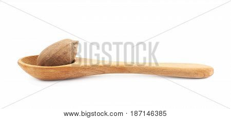 Wooden spoon and pecan nut composition isolated over the white background