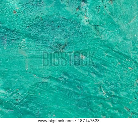 Plaster texture with lot of cracks and roughness. Abstract grunge background. Irregular structure painted in cold green. Aged wall surface with place for text.
