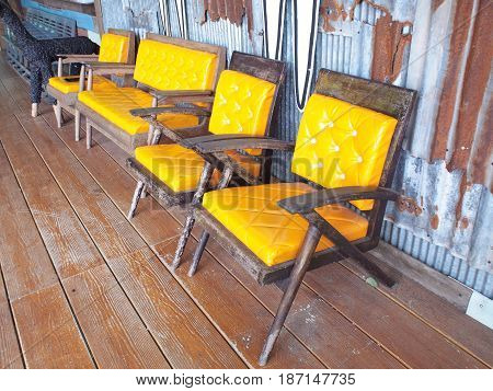 Set of vintage old wooden chairs with yellow cushion over rustic grunge wall.