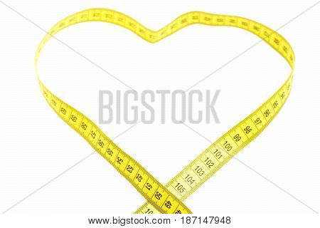yellow measuring tape in heart shaped isolated on white background