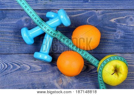 Orange, Apple, Measuring Tape And Weight Dumbbells For Diet Concept
