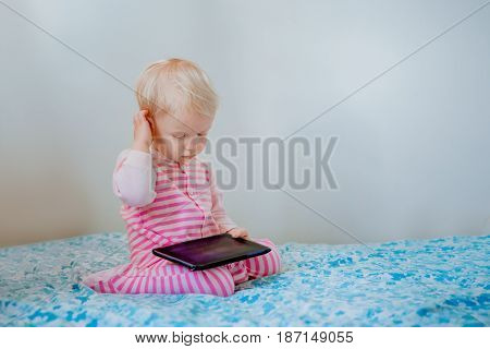 Cute adorable white Caucasian blond baby girl sitting in bed playing with digital tablet with funny face expression candid lifestyle early development new technology generation