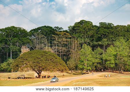 Siem Reap, Cambodia - February 2, 2016: Rural sandy road through fields and tropical forest with cars tuk-tuks and traveling tourists, Siem Reap province, Cambodia