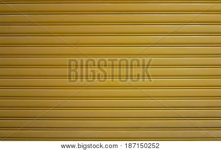 Old yellow zinc wall texture or old metal texture background. Steel door horizontal with pattern for design.