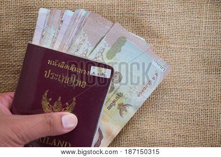 Thailand passport and thailand money 1000 baht in man hand