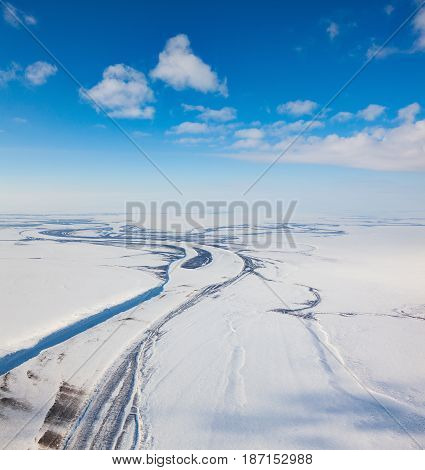 Aerial view above the river in endless tundra in winter time.