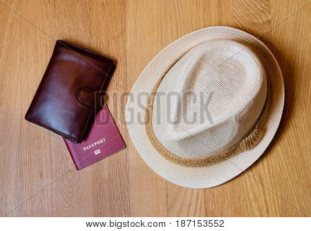 Travel accessories. Hat wallet passport on wooden background