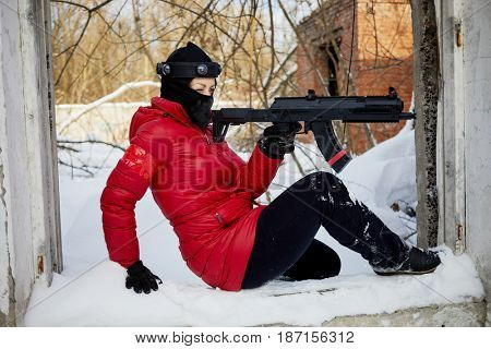 Woman in red jacket and ski mask aiming with gaming gun sitting on ground outdoor on winter day.