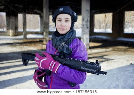 Teenage girl with gaming gun outdoor on winter day.