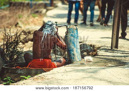 Sadhu is washed under running water near the road.