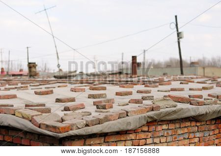Red bricks holding a tarp down onto a roof of a brick home in the city of Zhaodong China in Heilongjiang on an overcast day.