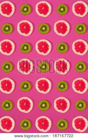 Grapefruit and kiwi pattern on pink background. Minimal flat lay concept. Print