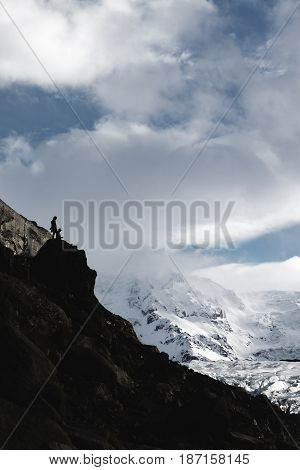 The silhouette of a climber with snow capped mountains in the background at Hvannadalshnúkur glacier in Iceland.
