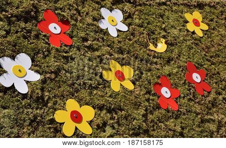 Artificial white, red and yellow flowers with a small artificial bird on artificial grass looking background