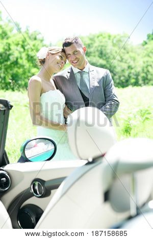 Bride and groom walking towards convertible car