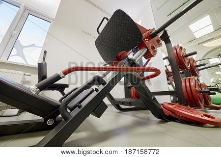 Leg press training machine in gym room.
