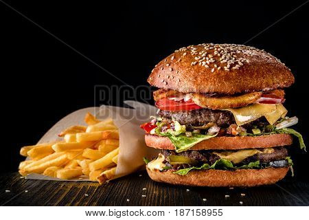 Craft beef burger and french fries on wooden table isolated on black background. Bar menu