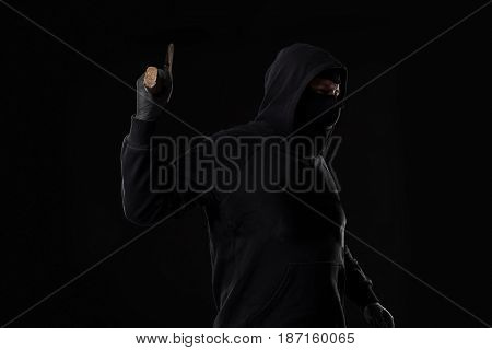 Bandit in black mask with hatchet on black background. Masked man with an ax
