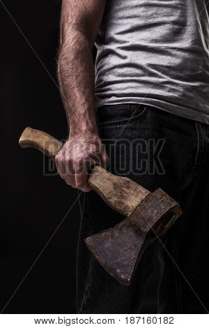 A man holds an ax in his hands against on black background. Criminal