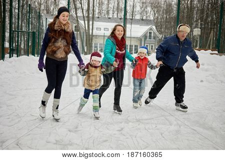 Family of five skates holdind hands at outdoor rink on winter day.