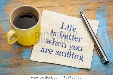 Life is better when you are smiling - inspirational handwriting on a napkin with a cup of espresso coffee