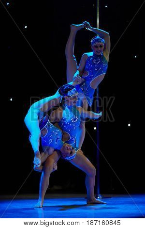MOSCOW, RUSSIA - FEB 11, 2017: Three smiling girls in blue dresses performs on stage of Korolevskiy concert hall during Pole Dance Show. Concert hall is designed for 750 spectators.