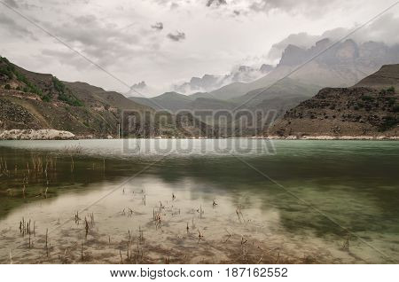 A beautiful mountain lake in the evening in cloudy weather with low rainy clouds