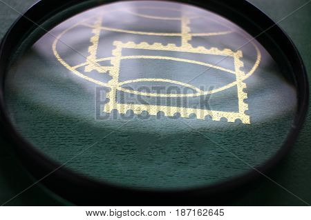 Magnifying glass on an album with postage stamps, look to focus