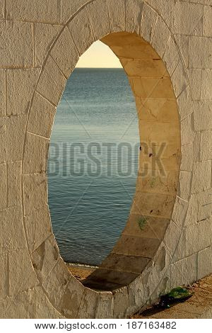 Round architectural window with the sea behind.