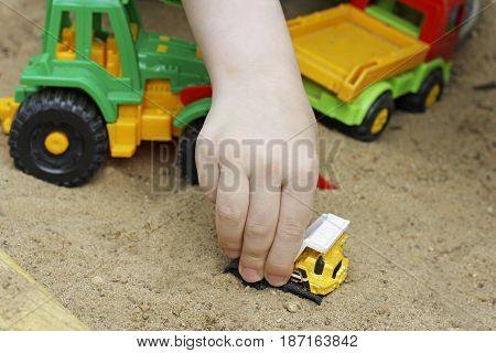Children in air in the warm season. The hand of a child playing with plastic building toy cars in the sand.