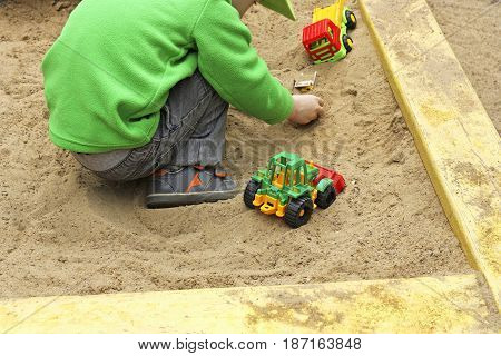 Children in air in the warm season. A child plays with plastic building toy cars in the sand.