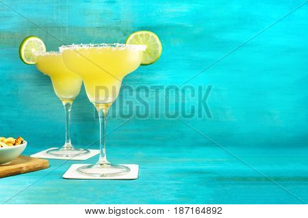 A photo of lemon Margarita cocktails with wedges of lime and a salted nuts snack, retro styled, with copy space