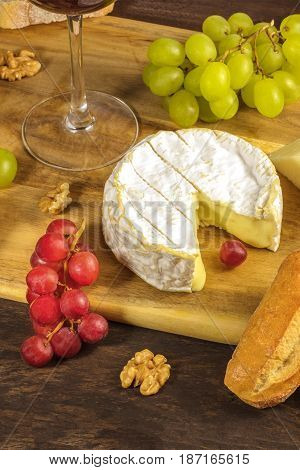 A photo of a camembert head at a wine tasting and pairing, with bread, purple grapes, walnuts, and a glass