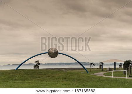 Napier New Zealand - March 9 2017: Metal Ecliptic sculpture by David Trubridge at beach park under heavy brown storm sky. Pacific Ocean and green lawn with some short trees.