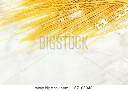 A closeup of spaghetti pasta with traces of flour, shot from above on a white marble texture with a place for text