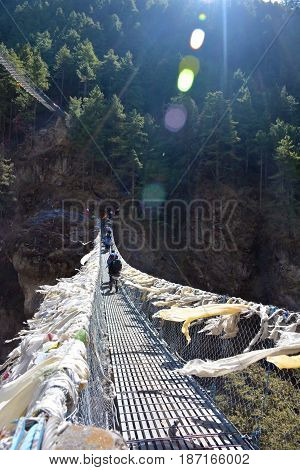 Group of tourists crossing high bridge in Himalayas Nepal. Lots of fluttering tibetian prayer flags.
