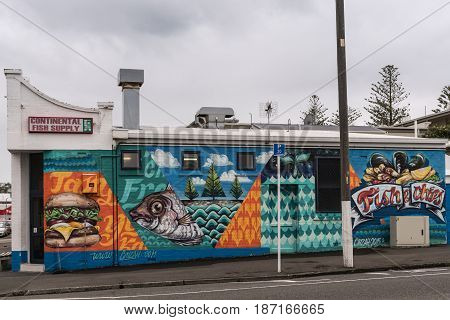 Napier New Zealand - March 9 2017: Continental Fish Supply is a corner store doing business as fish market and take-out. Located in folksy neighborhood. Street scene under silver sky. Colorful wall painting.