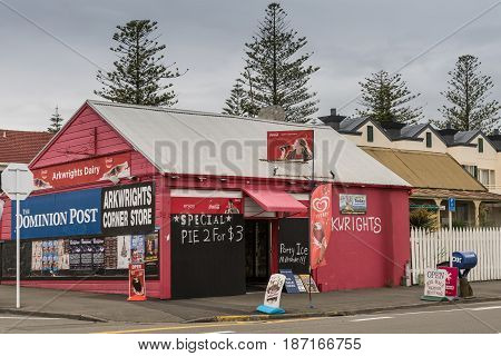 Napier New Zealand - March 9 2017: Arkwrights Dairy is a corner store selling groceries newspapers and basic household products. Red paint colored advertisement cloudy sky and neighborhood street scene.