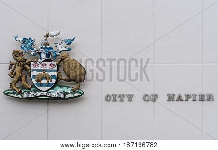 Napier New Zealand - March 9 2017: Closeup of colorful Coat of Arms and name of the city on the white wall of city hall.