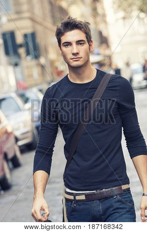 Beautiful model man with casual outfit outdoor in the street in the city center. The guy wearing a casual wear simple, long-sleeved tight, jeans and belt. A shoulder bag.