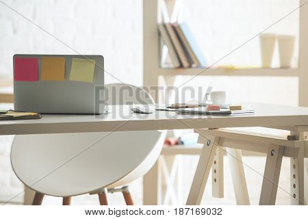 Back view of open laptop with sticker placed on modern office table with coffee cup supplies and other items
