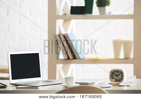 Bright office desktop with empty laptop clock coffee cup and other items. Blurry items in the background. Mock up