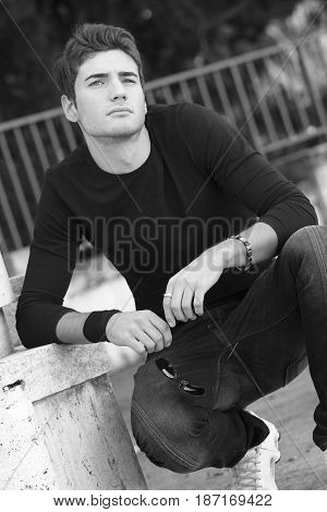 Handsome young man outdoor. Modern hairstyle. Behind him a natural park, leaning on a white wall squatting. Wrist band and long sleeved t-shirt. Thinking attitude. Black and white.