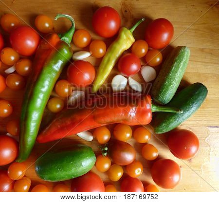 Vegetable background. Red ripe tomatoes, cherry, cucumbers, garlic and peppers in wooden table. Fresh organic products, pure eco food. Rural still life - closeup top view. Natural wallpaper.