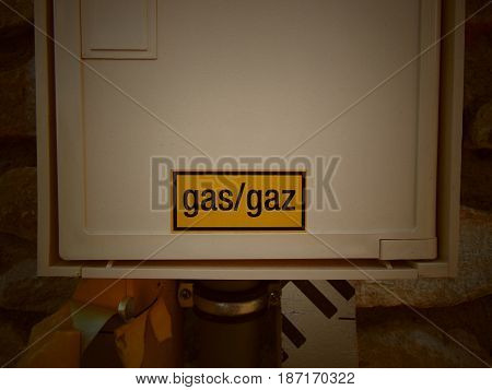 Yellow gas sign on white box of house outside