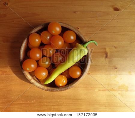 Cherry tomatoes and hot pepper in the bowl at the wooden table. Fresh organic products, pure eco food. Rural still life - new vegetables harvest. Natural ingredients, top view.
